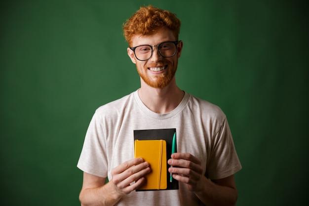 Portret uśmiechniętego readhead brodaty nerd, trzyma notatnika i pióra