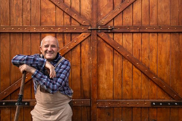 Portret uśmiechniętego rolnika stojącego przy drzwiach drewnianej stodoły lub spichlerza żywności na farmie zwierząt domowych.