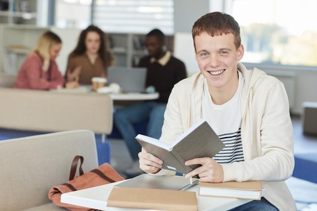 Portret uśmiechniętego rudowłosego chłopca podczas nauki w bibliotece uczelni i trzymania podręcznika,
