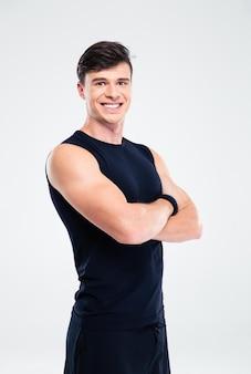 Portret uśmiechniętego sportowca stojącego z założonymi rękami na białym tle