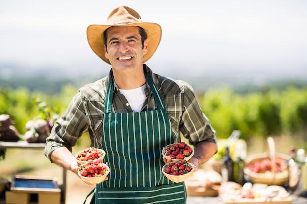Portret uśmiechniętego średniorolnego mienia puchary truskawki