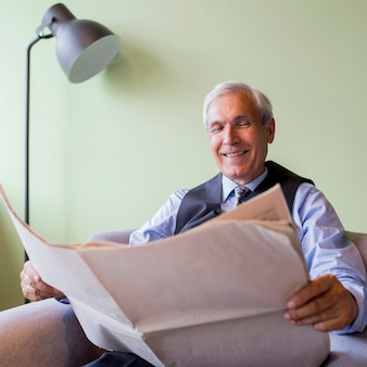 Portret uśmiechniętego starszego biznesmena czytelnicza gazeta