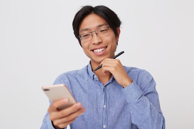 Portret uśmiechniętego sukcesu azjatyckiego młodego biznesmena w okularach i niebieskiej koszuli za pomocą telefonu komórkowego na białym tle nad białą ścianą