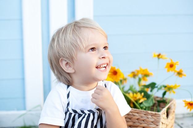 Portret uśmiechniętego szczęśliwego jasnowłosego chłopca dziecko cieszy się życiem. portret młodego chłopca w przyrodzie, park, na zewnątrz. pojęcie szczęśliwej rodziny i rodzicielstwa. koncepcja dzieciństwa. urocze dziecko. jesień