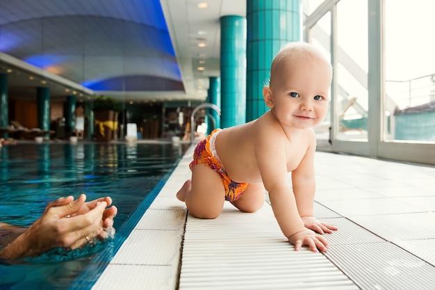 Portret uśmiechniętego, uroczego 11-miesięcznego dziecka w klasie na basenie