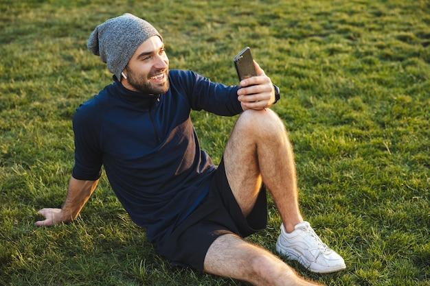 Portret uśmiechniętego wysportowanego mężczyzny ubranego w dres, używającego smartfona i siedzącego na trawie podczas treningu w zielonym parku