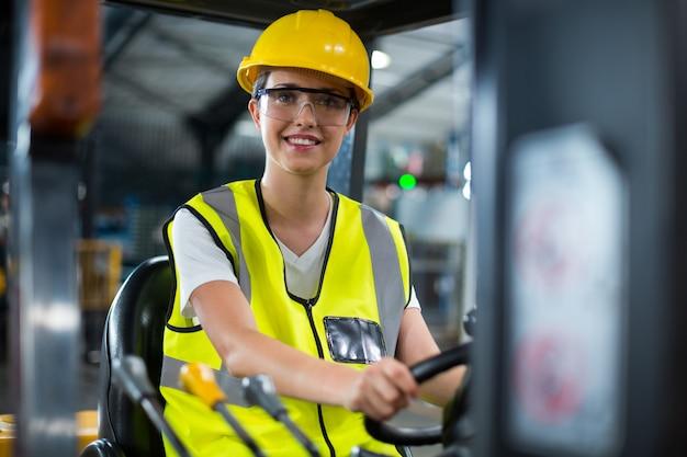 Portret uśmiechniętego żeńskiego pracownika fabrycznego napędowy wózek widłowy
