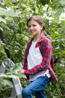 Portret uśmiechniętej 10-letniej dziewczynki stojącej na drabinie w sadzie