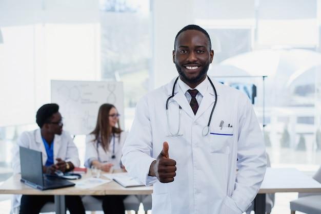 Portret uśmiechniętej afro amerykańskiej samiec doktorski pokazuje kciuk up podpisuje. asystent medyczny lub student w białym mundurze z stetoskop. przystojna samiec lekarka z medyczną grupą przy pokojem konferencyjnym.