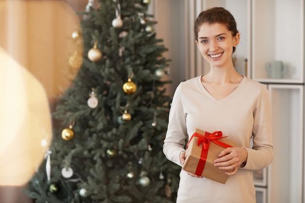 Portret uśmiechniętej atrakcyjnej młodej kobiety rasy kaukaskiej stojącej z prezentem bożonarodzeniowym...