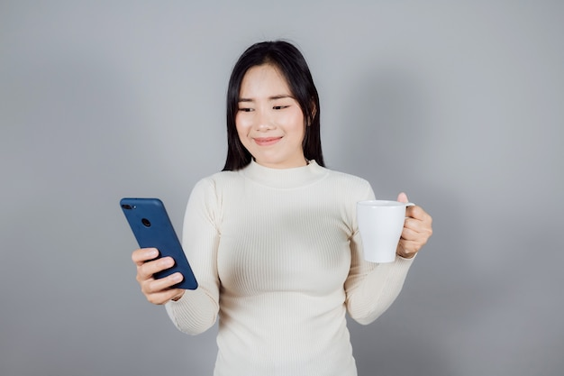 Portret uśmiechniętej azjatki nosi smartfona na szarym tle