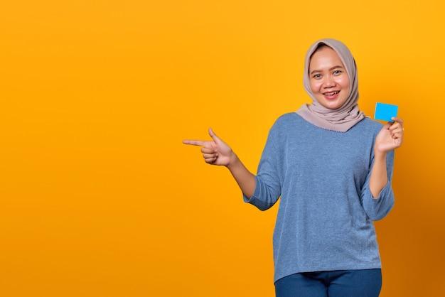 Portret uśmiechniętej azjatki trzymającej kartę kredytową i wskazującego palcem na pustą przestrzeń