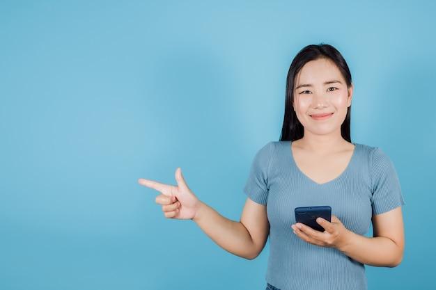 Portret uśmiechniętej azjatki trzymającej smartfona i wskazującego palcem w bok na niebieskim tle z miejscem na kopię