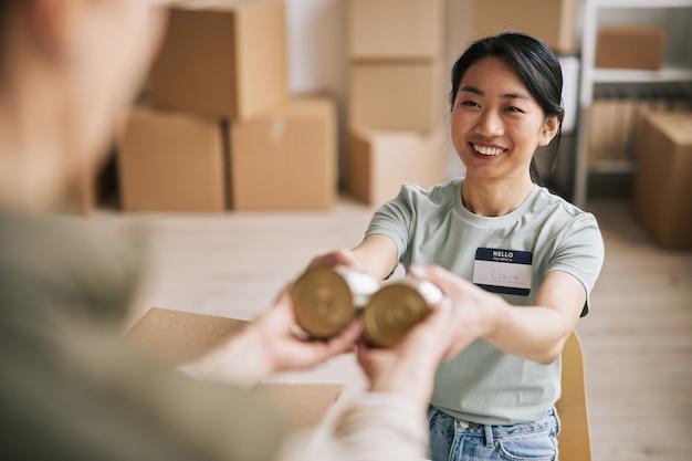 Portret uśmiechniętej azjatki wolontariatu podczas akcji pomocy i darowizn, pakowanie konserw w pudełka, kopiowanie przestrzeni