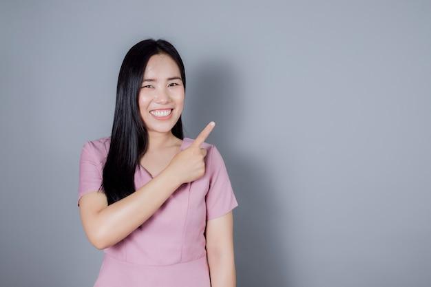 Portret uśmiechniętej azjatyckiej kobiety wskazującej palcem w bok na szarym tle