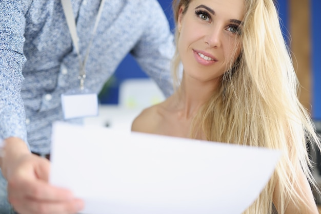 Portret uśmiechniętej bizneswoman, której kolega przyniósł dokument