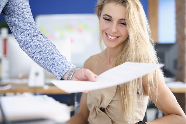 Portret uśmiechniętej bizneswoman, której kolega wręcza dokument biznesowy