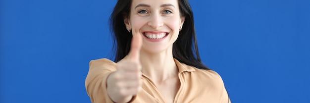 Portret uśmiechniętej bizneswoman pokazującej kciuk w górę gest