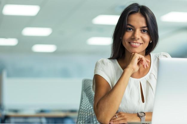 Portret uśmiechniętej bizneswoman pracującej w biurze