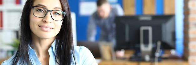 Portret uśmiechniętej bizneswoman w okularach w biurze