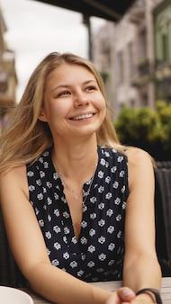 Portret uśmiechniętej blondynki siedzącej w kawiarni w pobliżu zielonych roślin - lato