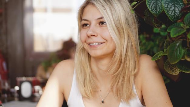 Portret uśmiechniętej blondynki siedzącej w kawiarni w pobliżu zielonych roślin