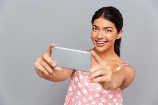 Portret uśmiechniętej brunetki kobiety w różowej sukience robi zdjęcie selfie na smartfonie odizolowanym na szarej ścianie