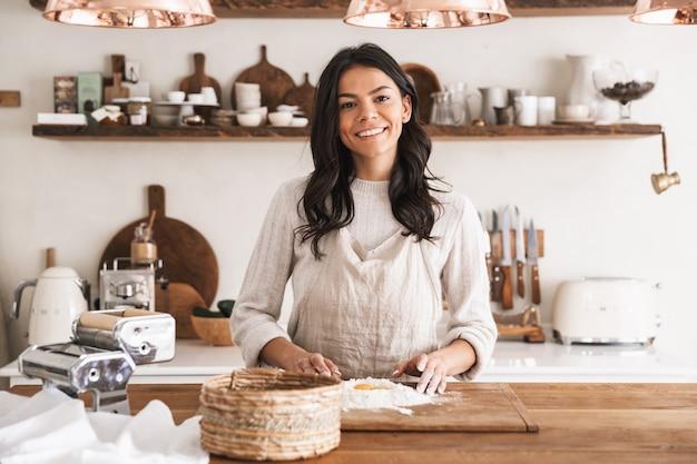 Portret uśmiechniętej brunetki w wieku 30 lat w fartuchu do gotowania ciasta z mąką i jajkami w kuchni w domu