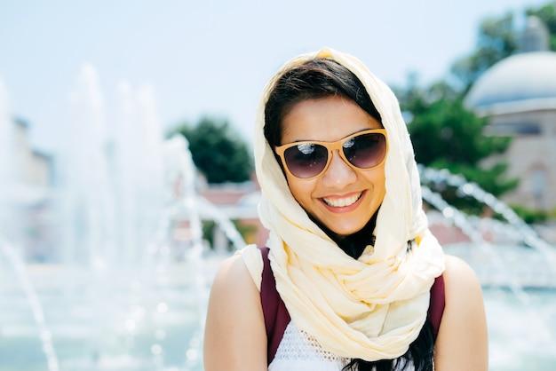 Portret uśmiechniętej ciemnowłosej dziewczyny w okularach przeciwsłonecznych w stambule na tle fontanny