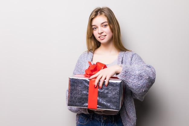 Portret uśmiechniętej cute teen girl otwarcia pudełko na białym tle