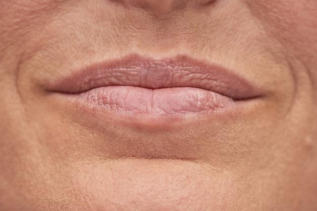 Portret uśmiechniętej dojrzałej kobiety o doskonałej skórze i pięknych ustach