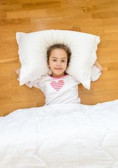 Portret uśmiechniętej dziewczynki leżącej na dużej poduszce na podłodze