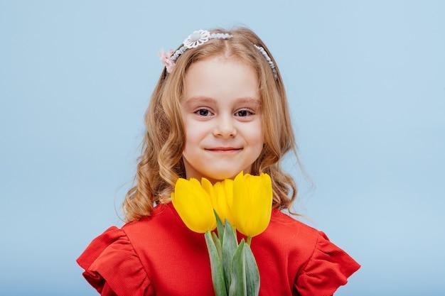 Portret uśmiechniętej dziewczynki z trzema żółtymi tulipanami, ubranej na czerwono, odizolowanej na niebiesko