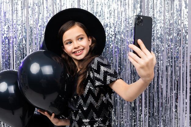 Portret uśmiechniętej dziewczyny na urodziny obchodzi selfie na smartfonie wśród czarnych balonów helem na błyszczącym