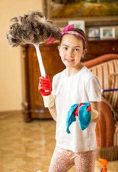 Portret uśmiechniętej dziewczyny pomagającej w pracach domowych i sprzątaniu