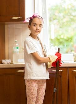 Portret uśmiechniętej dziewczyny pozującej na brudnej kuchni z miotłą i szufelką