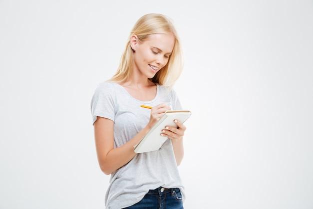 Portret uśmiechniętej dziewczyny robiącej notatki w notatniku na białym tle na białej ścianie