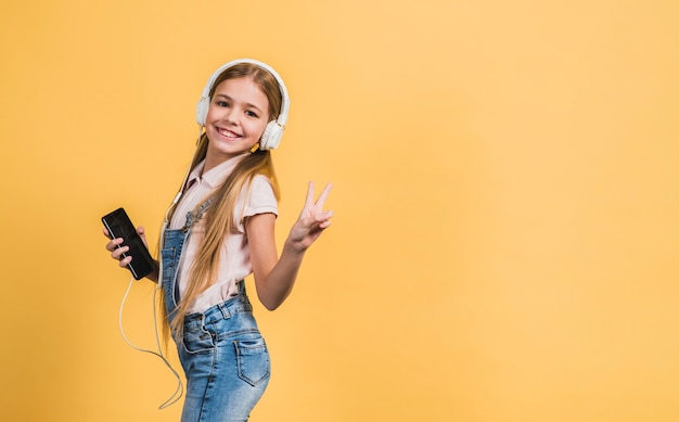 Portret uśmiechniętej dziewczyny słuchająca muzyka na białym hełmofonie gestykuluje przeciw żółtemu tłu