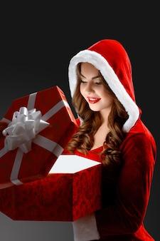 Portret uśmiechniętej dziewczyny smow, która otwiera prezent na nowy rok