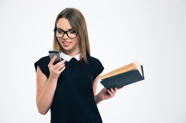 Portret uśmiechniętej dziewczyny trzymającej książkę i używającej smartfona na białym tle