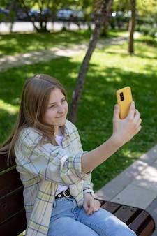Portret uśmiechniętej dziewczyny trzymającej smartfona, robiącej selfie podczas rozmowy wideo ze znajomymi