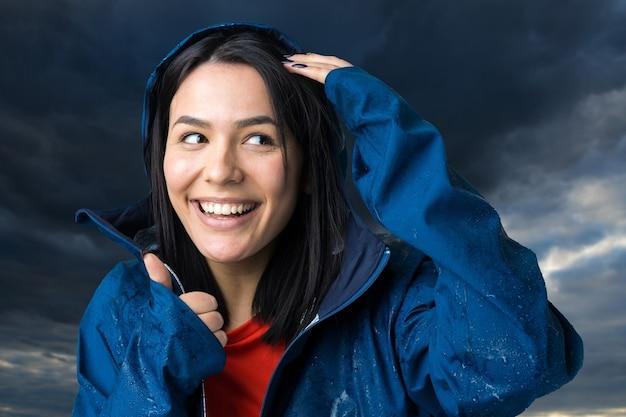 Portret uśmiechniętej dziewczyny ubranej w niebieski płaszcz przeciwdeszczowy w krople pozującej z kapturem