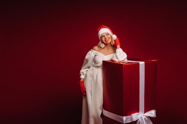 Portret uśmiechniętej dziewczyny w białej sukni i czapce mikołaja z ogromnym prezentem świątecznym na czerwono.
