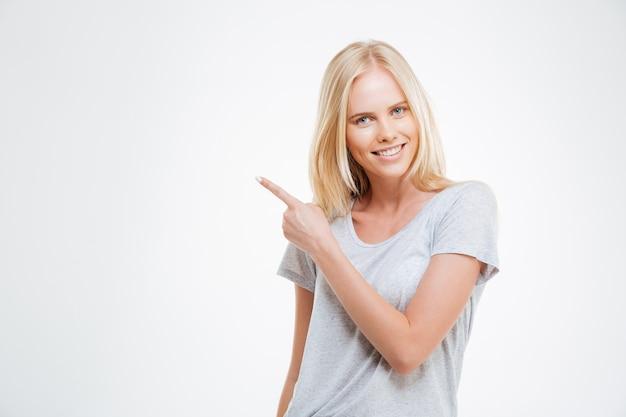 Portret uśmiechniętej dziewczyny wskazującej palcem na białym tle na białej ścianie
