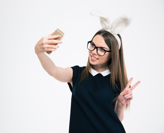 Portret uśmiechniętej dziewczyny z uszami królika, która robi zdjęcie selfie na smartfonie na białym tle