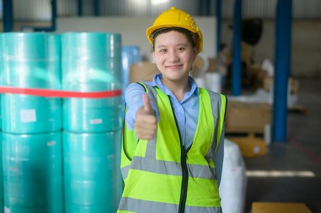 Portret uśmiechniętej inżynierki z azji pracuje w nowoczesnym magazynie