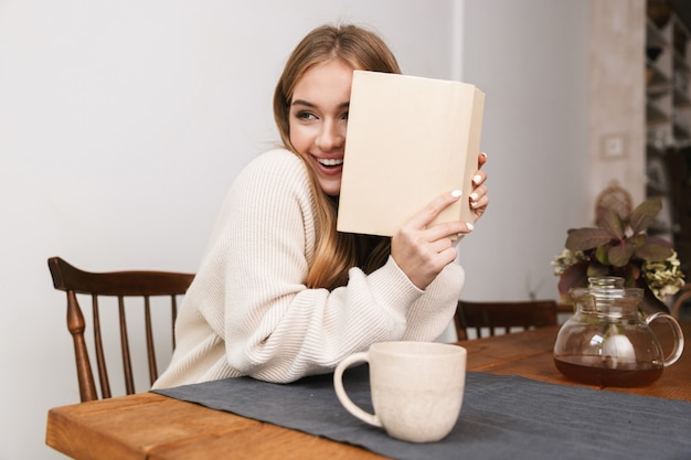 Portret uśmiechniętej kaukaskiej kobiety noszącej zwykłe ubrania, czytającej książkę i pijącej herbatę w przytulnym pokoju