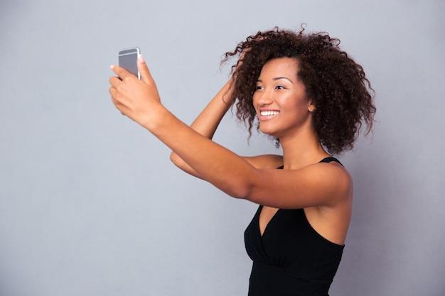 Portret uśmiechniętej kobiety afro american co selfie zdjęcie na smartfonie na szarej ścianie