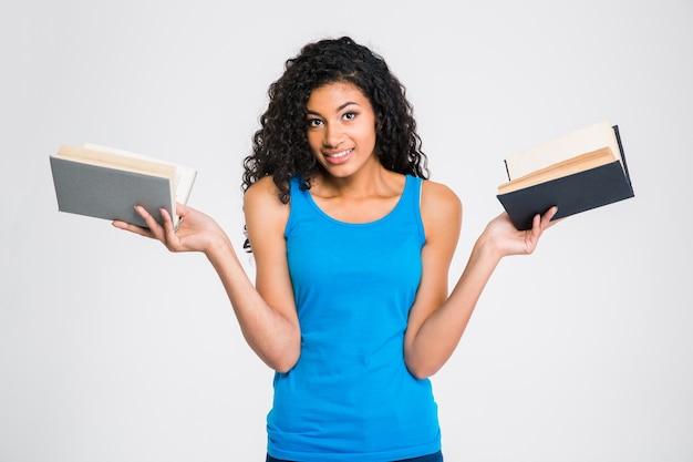 Portret uśmiechniętej kobiety afro american posiadającej dwie książki na białym tle na białej ścianie