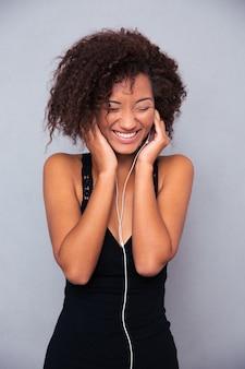 Portret uśmiechniętej kobiety afro american słuchanie muzyki w słuchawkach na szarej ścianie